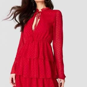 En röd långärmad klänning från Linn Ahlborg X NA-KD kollektionen, i storlek 34. Säljer då den inte kommer till användning. Använd en gång