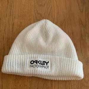 Vit sotarmössa från märket Oakley.