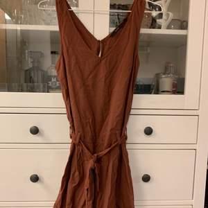 En playsuit i brun/rött färg. Helt ny och aldrig använd. Köpare står för frakt om upphämtning ej är ett alternativ.