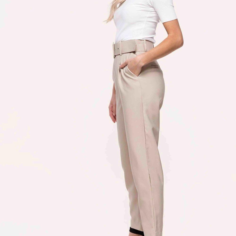 Beiga byxor köpta från Loavies med tillhörande skärp. Aldrig använda. Ser gråa ut på bilden men är beiga.  Kan mötas upp i Västerås eller skickas mot att köparen betalar frakten. . Jeans & Byxor.