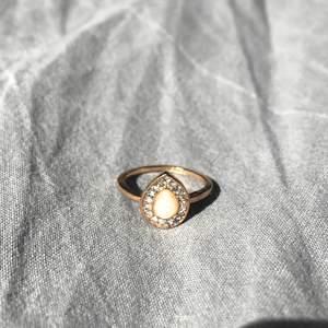 Guldig ring med stor sten i mitten och mindre diamanter runt🥰
