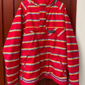 Röd snowboardjacka ifrån Burton med blå och gula detaljer passar perfekt för dig som vill hållas varm i skidbacken  Köparen står för frakt, kan även mötas upp i Borlänge eller Örebro