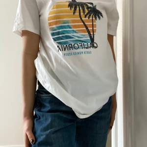 En vit T-shirt med ett fint tryck. Beställd från Nelly men aldrig fått användning för tröjan. Somrig och vintage style. Oversized i storlek Xs men passar såklart större.  Buda och kontakta mig!🤩