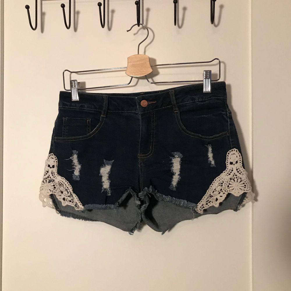 Ett par mörkblåa jeansshorts med spetsdetaljer! Köpta från Rut&Circle i storlek 38! 🌟 köparen står för frakt 😇. Shorts.