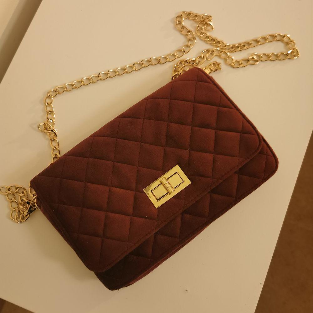 Oanvänd vinröd väska med gulddetaljer. Frakt ingår i priset ❤️. Väskor.