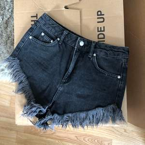 Korta svarta shorts med fransar