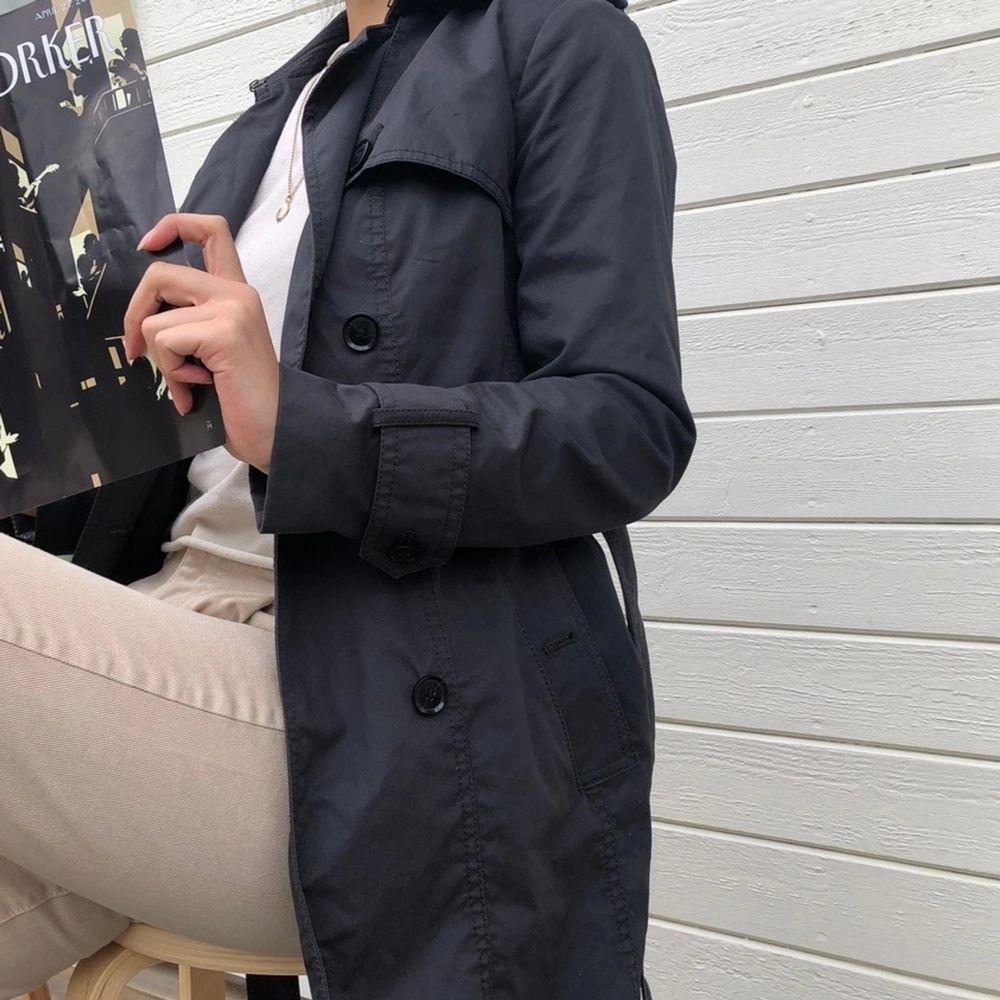 Sparsamt använd trench coat från Banana Republic i mörkgrå. En inneficka, två ytterfickor samt medhörande skärp. Vattenresistent yttermaterial i bomull och polyester. Strl. XS och normal i passformen. Ordinarie pris: 2589 kr. Modellen är 164 cm. . Jackor.