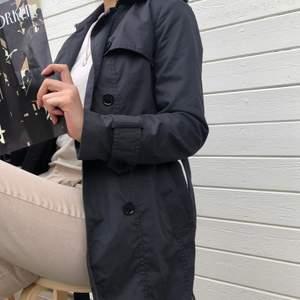 Sparsamt använd trench coat från Banana Republic i mörkgrå. En inneficka, två ytterfickor samt medhörande skärp. Vattenresistent yttermaterial i bomull och polyester. Strl. XS och normal i passformen. Ordinarie pris: 2589 kr. Modellen är 164 cm.