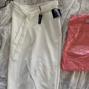 Vit knälång kjol med slits framtill från Nelly.com, Kjolen är helt oanvänd men behöver strykas. Den passar både någon med storlek S eller M.😊 Köparen står för frakten.