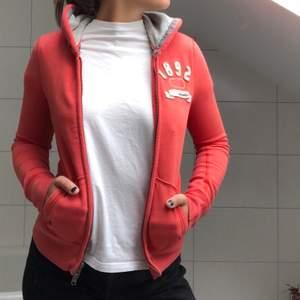 En snygg orange hoodie från Abercrombie. Ljusgrå insida av huven och lite vit text på vänster sida!