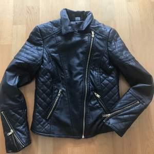 Nästan oanvänd kort jacka som ser ut som skin, men är 100% polyester. Avtagbar krage i 'oäkta' päls. Storlek 36. Färg svart.