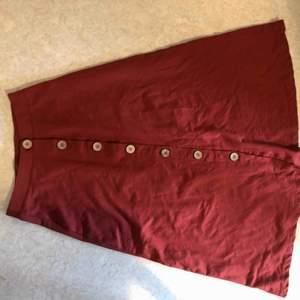 Superfin roströd kjol med träknappar, faller fint då den är lite klockad. Går just ovanför knät på mig som är 168cm