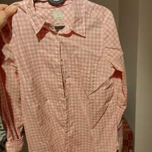 En rosarutig skjorta som är köpt på Gap i USA. Använd men är i väldigt fint skick. Storlek S men skulle våga påstå att den passar även M.