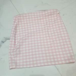 En kort rutig rosa kjol i storlek medium men den är väldigt liten så skulle säga att den passar någon som är small.