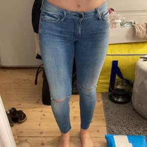 """Ett par ljusblåa jeans från Crocker. Det är hål vid knäna, och ett på smalbenet även lite """"slitningar"""". Jag är 160cm och dom passar min längd, kanske några cm längre också. Storlek W:26 L32"""