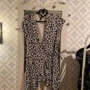 Kort klänning med leopardmönster från H&M ca 2år gammal endast använd fåtal gånger. Storlek 36 men uppfattas lite mindre. Den har en knytdetalj vid midjan. Nypris 299kr, mitt pris 150kr!