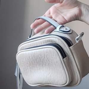 Beige väska i fakeskinn med vita och silvriga detaljer. Kan användas med eller utan axelrem, kan justeras och användas som midjeväska om man vill. ✨Köpare står för frakt på 66kr.