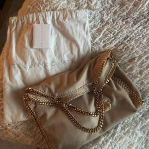 Så fin  beige Stella mccartney väska med guldiga kedjor, aldrig använd!! Har dustbag och äkthets bevis💕💕 den är väldigt speciell då Stella väskorna ofta har silvriga kedjor. buda från 3000