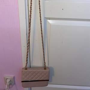 En rosa och guldig liten väska som är lätt att ta med t.ex när man ska åka iväg och shoppa. Även perfekt att förvara saker i. Använd men i fint skick. Inuti har den en liten ficka med dragkedja.