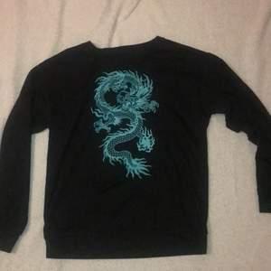 En svart sweatshirt med ett blått tryck i storlek s.