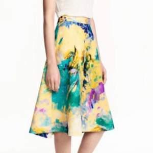 En fin midi kjol från H&M med vattenfärgs tryck! Mycket fint och aldrig använd. Skriv privat vid intresse! Köpare står för frakten.