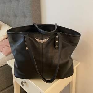 En större väska från Zadig & Voltaire, Modellen heter Mick Bag. Svart läder, rymlig och snygg! Den är knappt använd och därför säljer jag den då den bara hänger hemma! Inköpt på Zadig & Voltaire butiken i Köpenhamn 2018 för 2605DKK vilket ungefär är 3500kr☺️ Jättefint skick, som ny! Säljer för 1800, eller buda gärna så kan pris diskuteras!