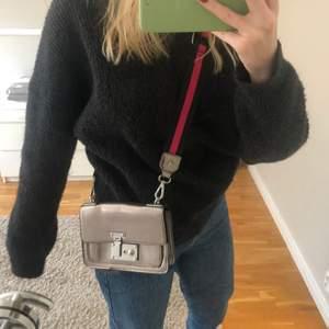 Jätte cool silvrig väska med rosa/svart tillhörande band. Bandet går att ta av. Väskan är i mycket bra skick, använd ett fåtal gånger. Har justerbart band så man kan göra den både kortare och längre.                                                                                  Köparen står för frakt.
