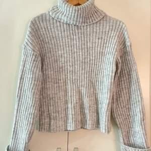 En ribbad, stickad turtleneck i väldigt fin grå färg (ingen fläck, tröjan skiftar i grå färg). Supervarm med bredare (nertill) och lite längre ärmar. Välanvänd, men i väldigt bra skick!  Nypris: 399kr, mitt pris 200kr