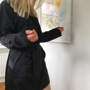 En svart blazer/klänning ifrån Bik Bok i satintyg. Knyte i midjan. Aldrig använd.