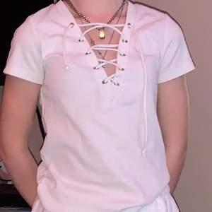 En fin vit t-shirt med snörad urringning. Bra kvalitet, inte använd alls mycket. Snörena är lite ojämna men det går att fixa!💕