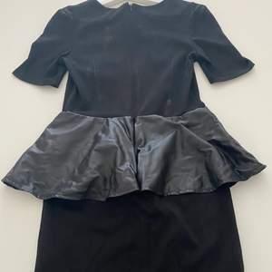 En svart klänning som är ca knä längd.