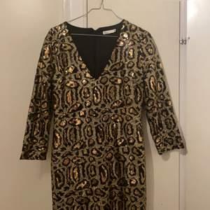 Säljer denhär fina svart och guld palljerade klänningen. ALDRIG ANVÄNT!