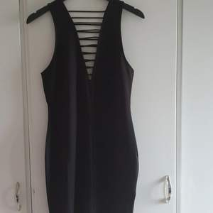 Kort figursydd svart klänning. Djup urringning fram och bak.