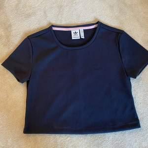Säljer en marinblå T-shirt med text på ryggen från adidas. T-shirten är lite kortare i modellen. Bra skick då den är använd max 3 gånger.   Köparen står för frakt.