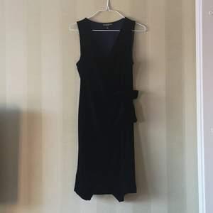 Wrap-klänning i mörkblå sammet. Använd en gång. Hör av dig om du vill ha fler bilder eller undrar något! Fri frakt och använder plicksafe om så önskas🌟