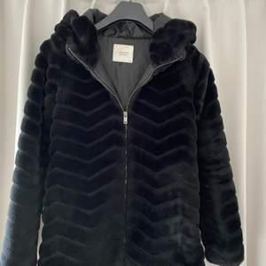 Nästan som ny, svart fuskpälsjacka med luva och dragkedja stlk xs