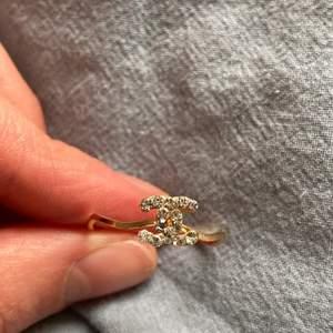 Superfin ring med chanell-märket i strass. Obs ej äkta Chanel!!!!! Lite vågigt band på ringen! Ca 2 som i diameter.