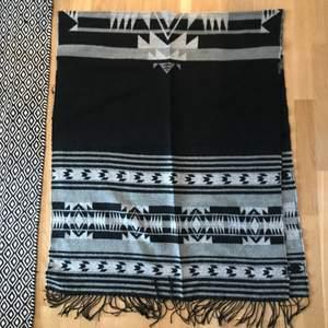 En varm stor halsduk gråmönstrad och svart med svarta fransar 200 cm x 78 cm med svarta fransar