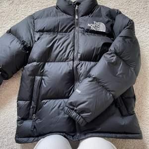 """Jag säljer min the north face puffer jacket. Jag köpte den för knappt en månad sen på the north face hemsida, kvitto finns. Den är i en """"youth"""" storlek L men sitter stort så motsvarar en S i dam storlek. Köpt för 2600. Inga defekter."""