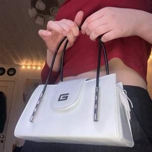 GRATIS FRAKT! en gullig mini väska med ett silvrigt g på framsidan. inte helt säker vart den är ifrån men det ser like ut som guess (?) ganska liten men rymmer det mesta som mobil, plånbok å sånt! passar till jättemycket kläder då den är svart och vit och den är perfekt till sommaren ☀️ (OBS det blir budgivning om flera är intresserade såklart☺️)