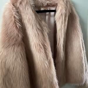 Fake ljusrosa pälsjacka från H&M med stort tryck på ryggen. Kort i passformen. Använd få gånger