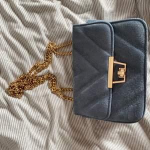 Blå axelbandsväska med guldkedja. Köpt på Nelly för ett tag sen men knappt använt. Nypris var 349kr. Man kan ändra banden så dom blir långa istället. Köparen står för frakten