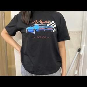 Svart t-shirt med snyggt tryck som aldrig kommit till användning. Frakt tillkommer