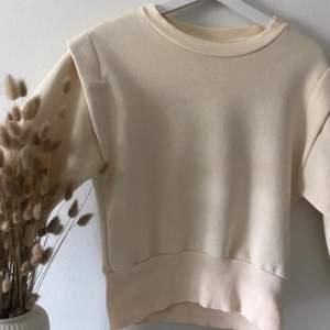 En beige sweatshirt från Gina Tricot med coola detaljer vid axlarna och ner till vid midjan. Säljs pga brist på användning 💖