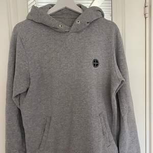En ljusgrå hoodie från Jack&Jones i storlek L, dock saknar hoodien snöret till luvan!