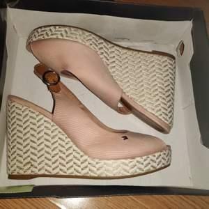 Ljusrosa sandaler med kilklack. Inte mycket använda men tecken på användning finns pga att dom är så ljusa så minsta lilla syns. Går säkerligen att göra dom helt rena hos t.ex skomakare eller med skumtvätt. Bekväma att gå i trotts den höga hälen. Storlek 38