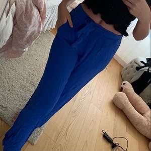 Säljer dessa klarblåa byxorna med knyt och breda stuprör ben, storlek 36. Aldrig använda där av måste strykas då de legat nere i en låda. Formar sig jättefint vid rumpan. Säljer för 70 kr. Köparen står för frakten!