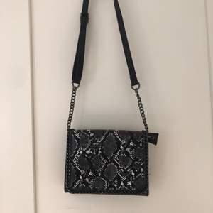 En svart och grå väska med orm mönster.
