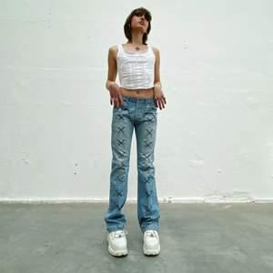 Lee secondhand-jeans med mörkblå snörning. Designade av Ezzie i samarbete med Ebba Martin. (Shipping only within Sweden)