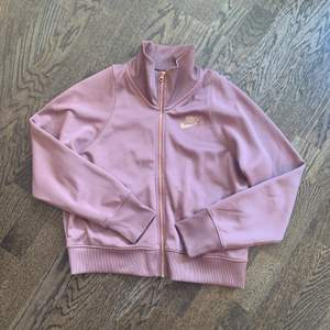 Stylish Nike training jacket in a nice berry tone, with zipper and details in rosé gold. The jacket is in a good condition and hasn't been worn many times. It's 87% polyester, 13% cotton, 3% elastane.